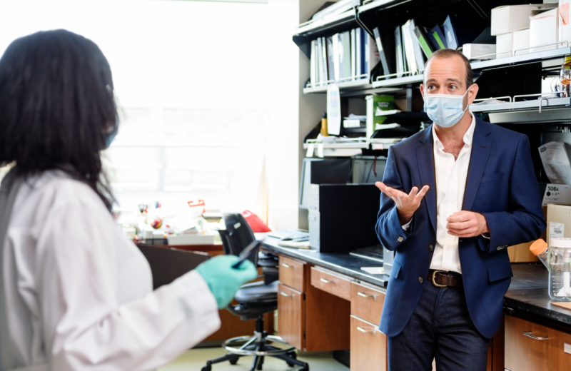 Leor Weinberger wearing a mask in the lab talking to another scientist